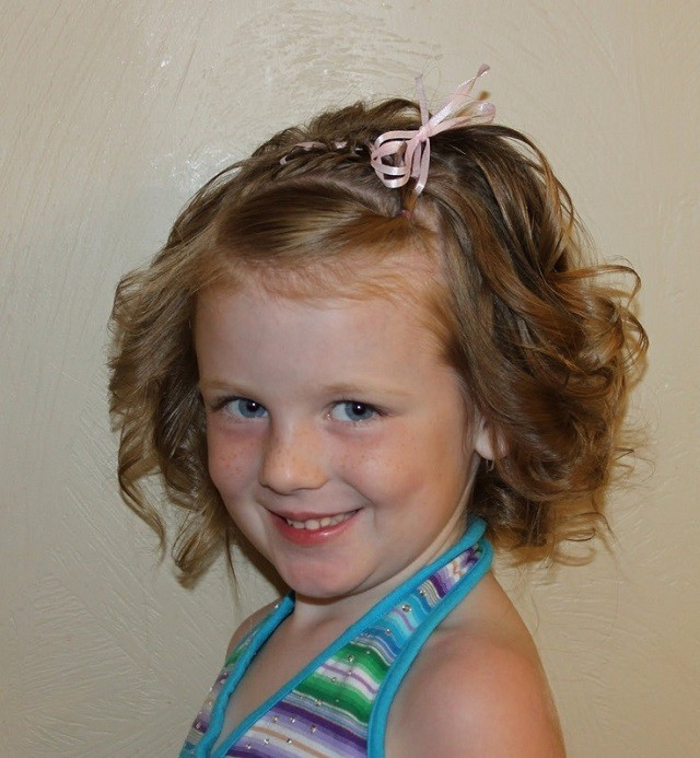 una trenza marcando una trenza para esta nia sonriente que luce un peinado muy bonito rematado por un moo de color rosa