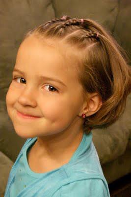 Tres trenzas cosidas forman este peinado de niña muy bonito.