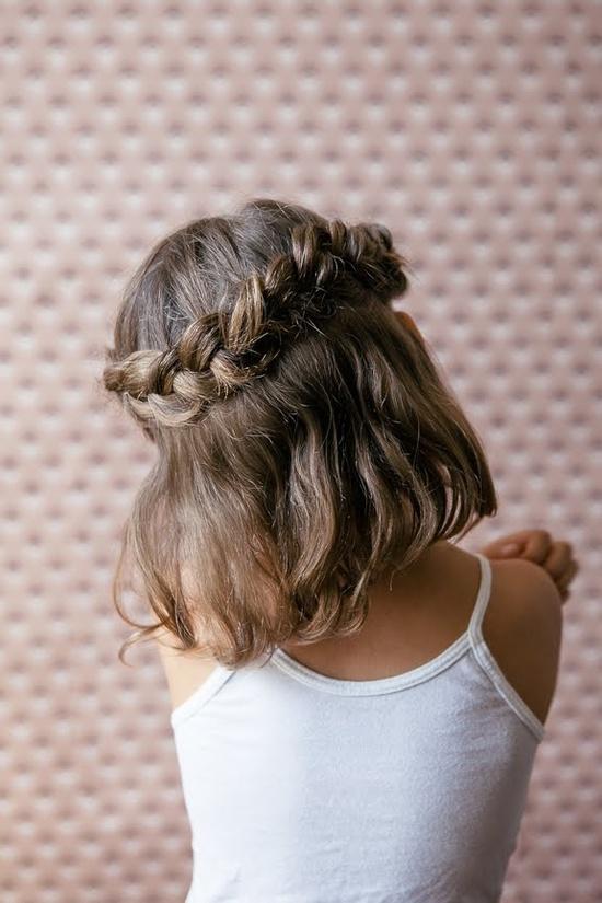Una corona sencilla realizada con trenzas que sostienen la melenita  preciosa de esta niña.